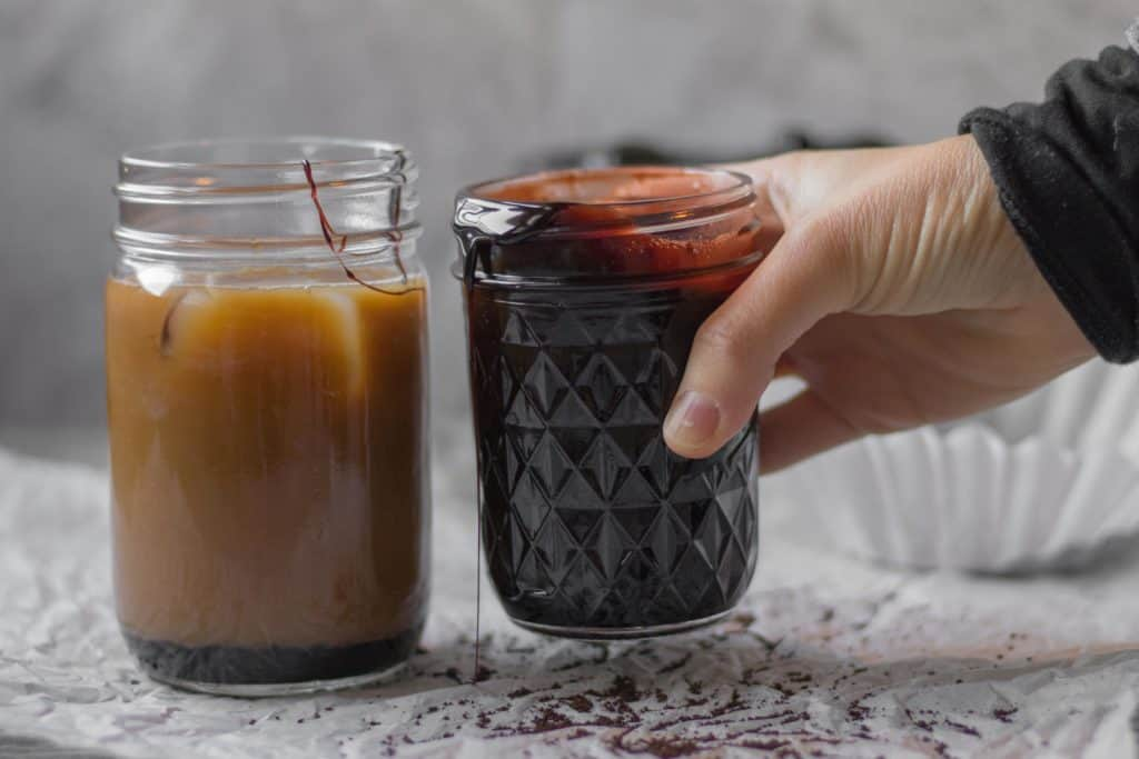iced coffee in a glass jar with homemade chocolate syrup being held by a hand