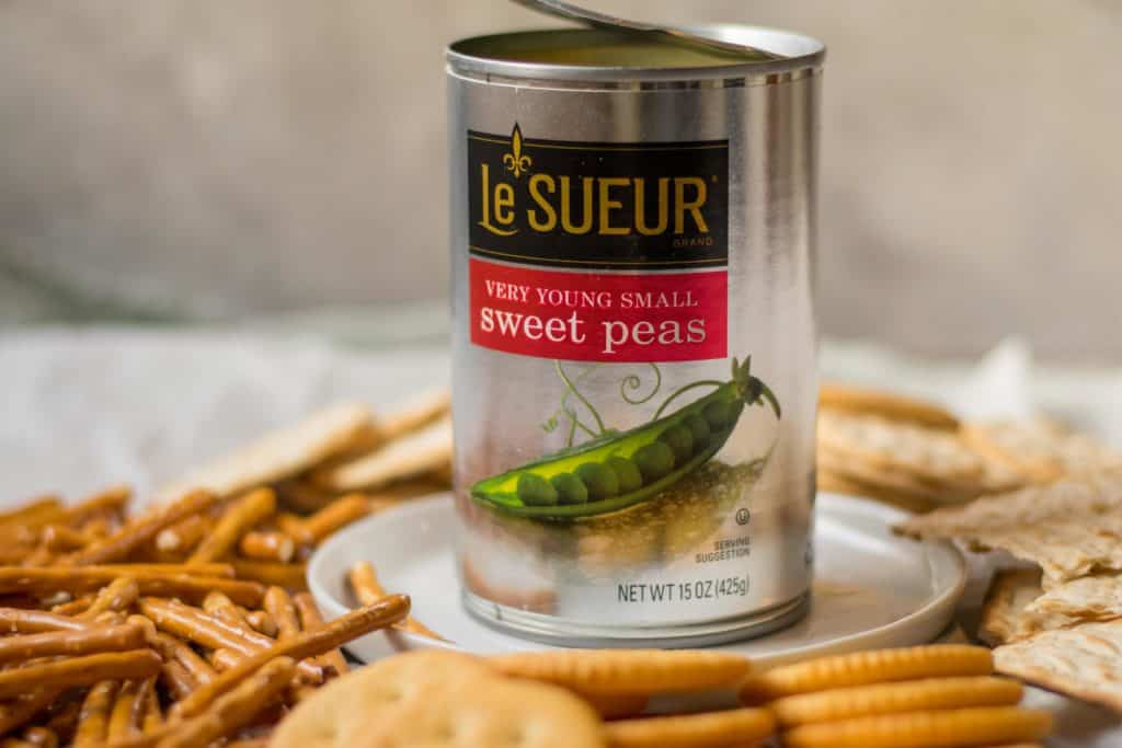 can of lesuer peas on a plate surrounded by crunchy snacks
