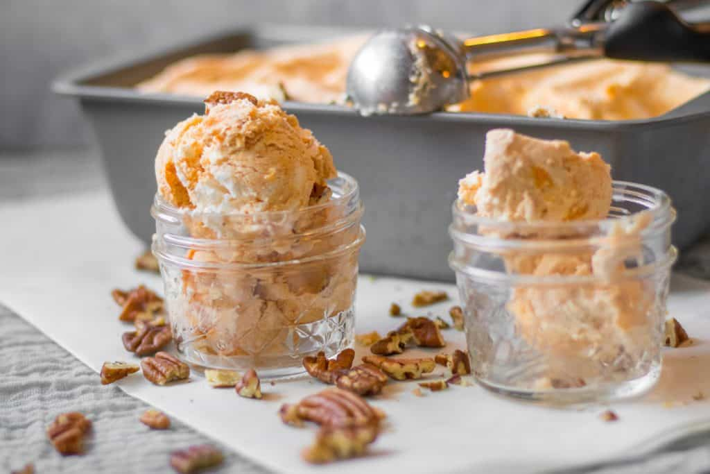 scooped no churn pumpkin ice cream in small mason jars with walnuts scattered around