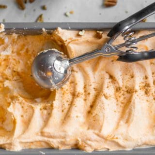 no churn pumpkin ice cream in a loaf pan with scoop