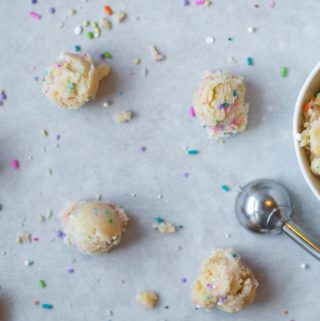 edible sugar cookie dough with sprinkles in a bowl and in balls with a small cookie scoop