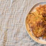 potato latkes on a plate with applesauce