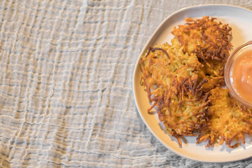 potato latkes on a plate with applesauce