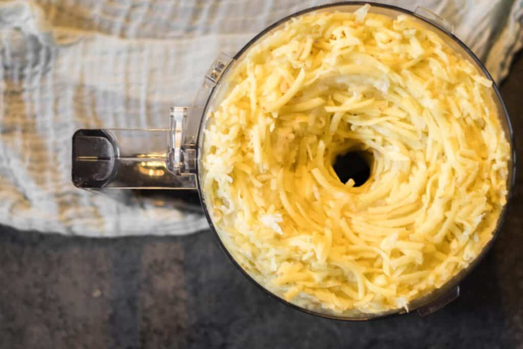 shredded potatos in the bowl of a food processor