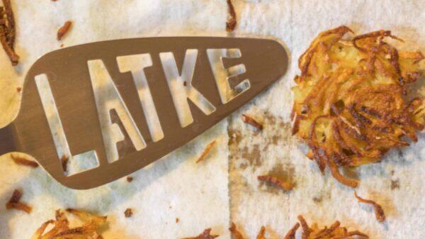 three potato latkes with a spatula that says latke