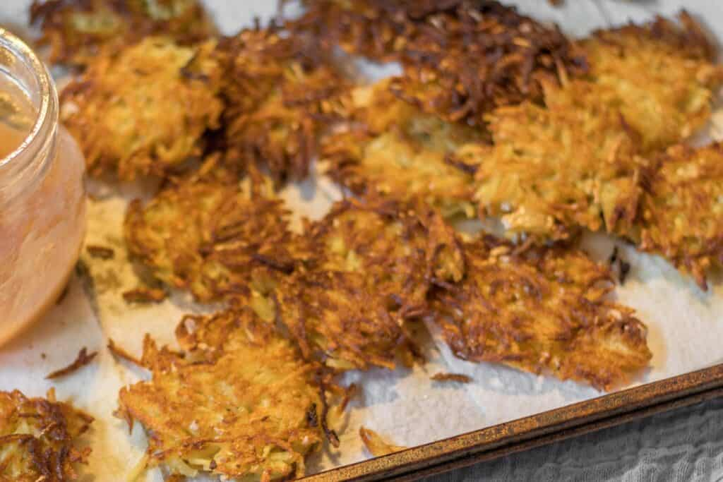 lots of latkes on a baking sheet lined with paper towel
