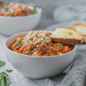 side view of bowl of minestrone soup with cheesy toast resting on top