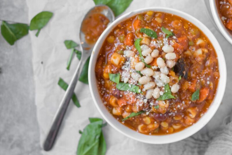 bowl of minestrone soup garnished with herbs, parmesan and white beans
