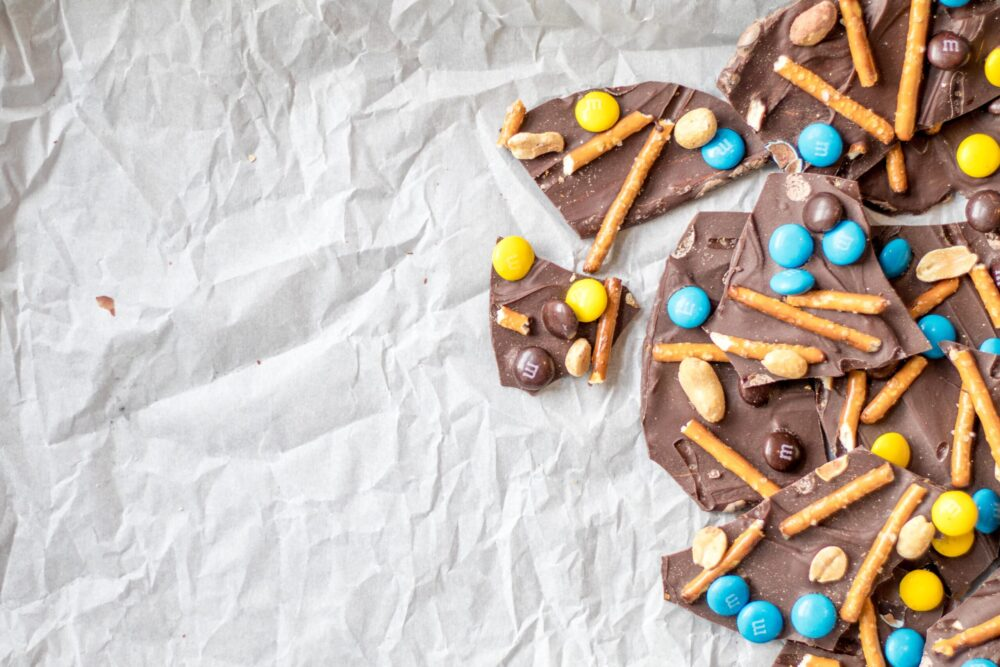 chocolate bark with m&ms, pretzels and salted peanuts on parchment paper