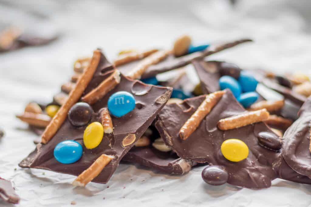 close up of chocolate bark with m&ms pretzels and peanuts