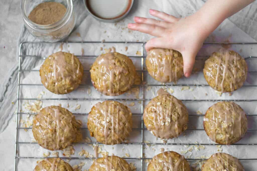 kids hand grabbing a chai spice muffin off a cooling rack