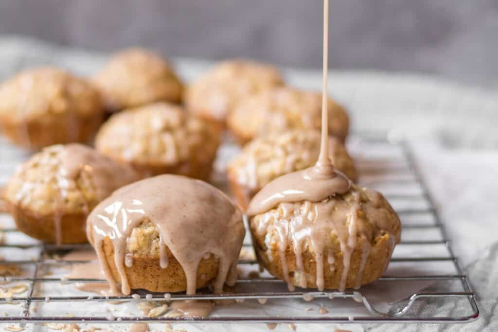 muffins with chai spice glaze being poured over them