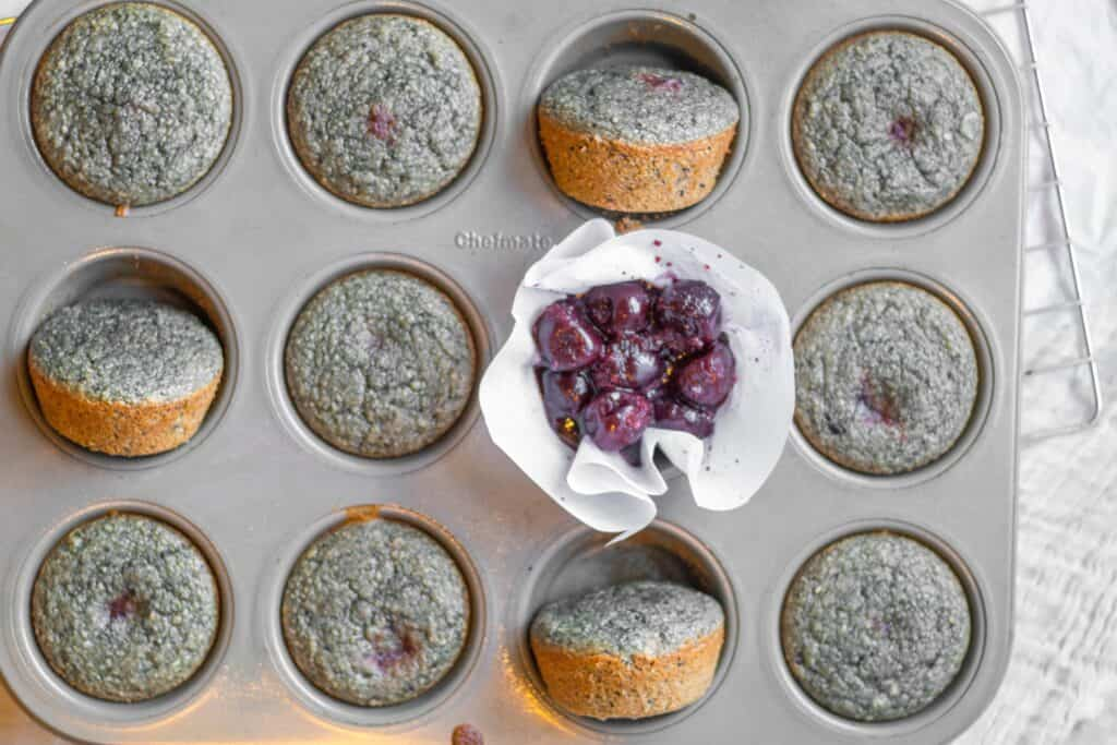 baked muffins in a muffin tin with raw cherries in one of the spots