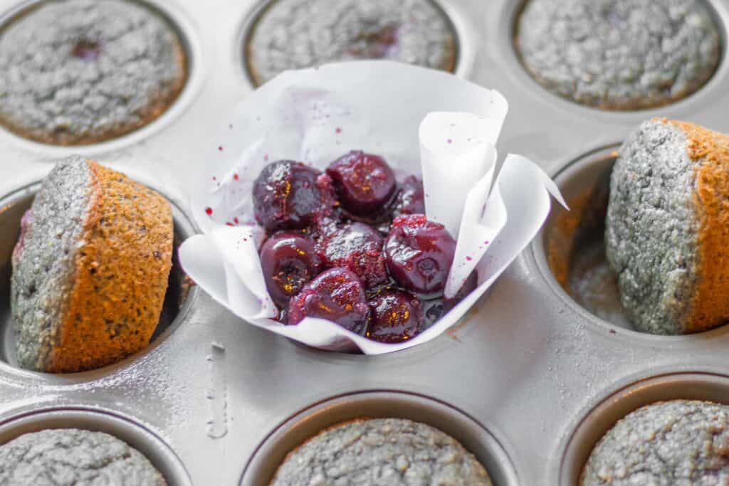 frozen cherries in a muffin tin with baked muffins