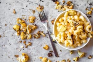 bowl of cauliflower mac 'n cheese with roasted cauliflower on parchment paper with a silver fork