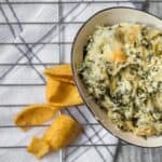 bowl of spinach artichoke dip with corn chips spread around