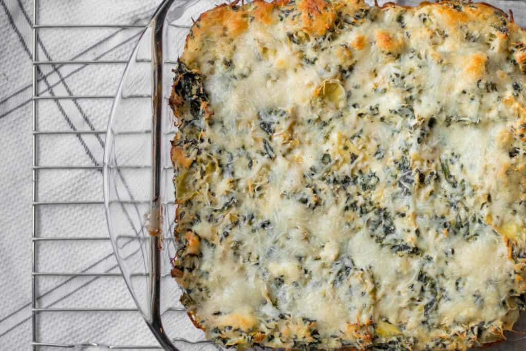 glass dish with baked spinach artichoke dip