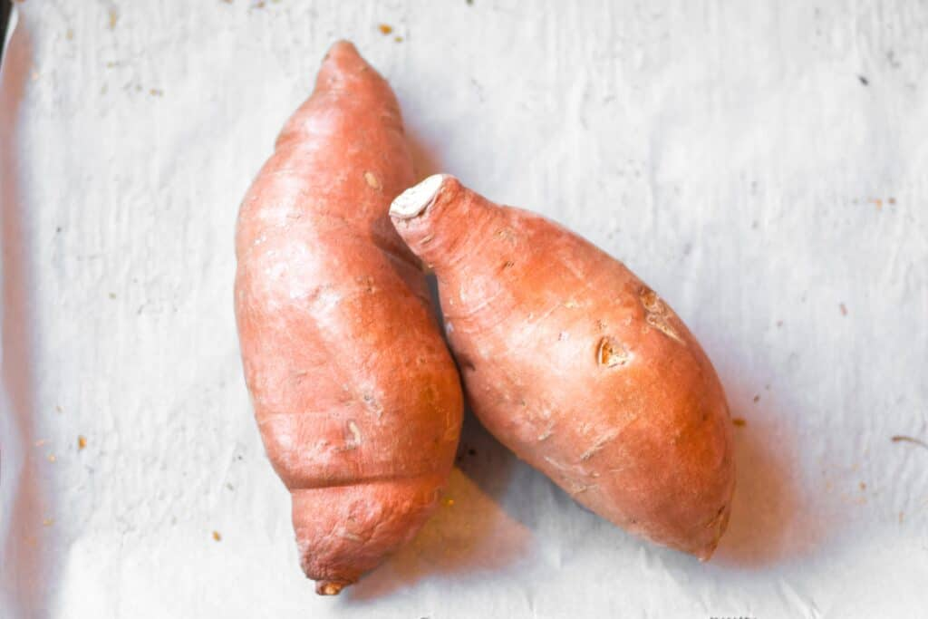 two sweet potatoes on a baking sheet