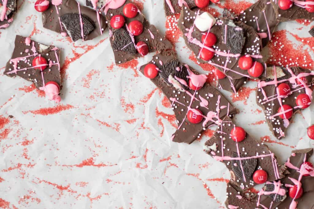 chocolate bark with red m&m's, pink drizzle, and crushed oreos