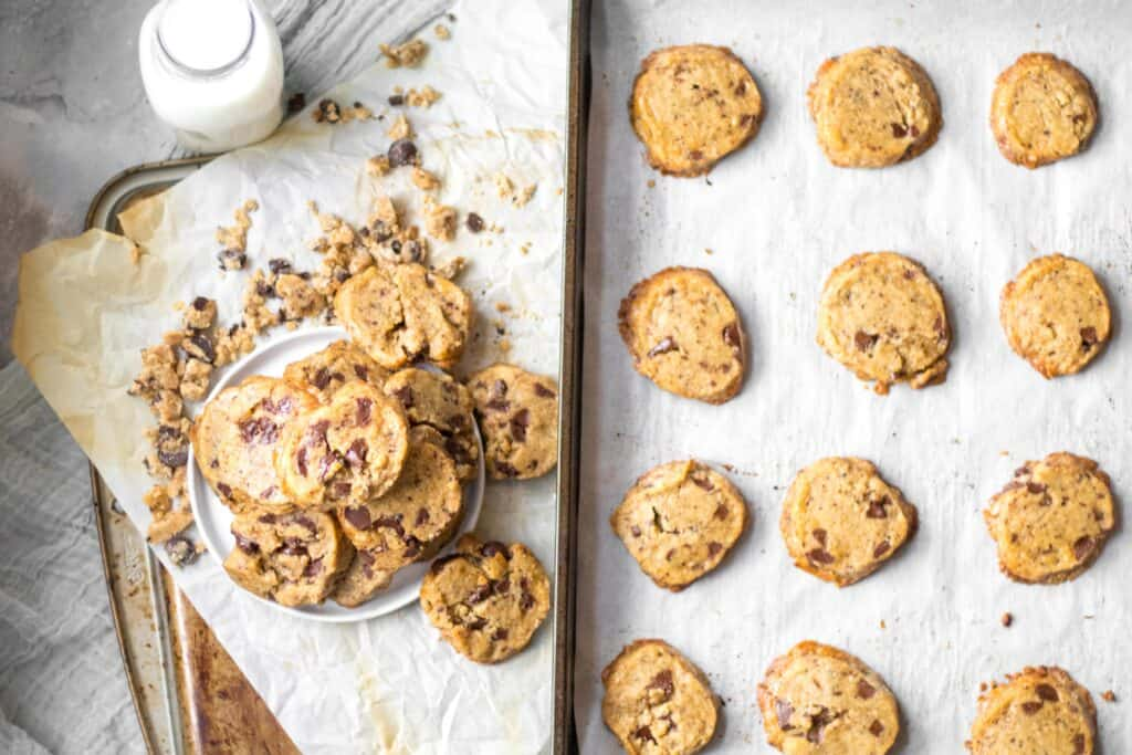 cookies piled on a plate next to a baking tray of cookies with a jar of milk