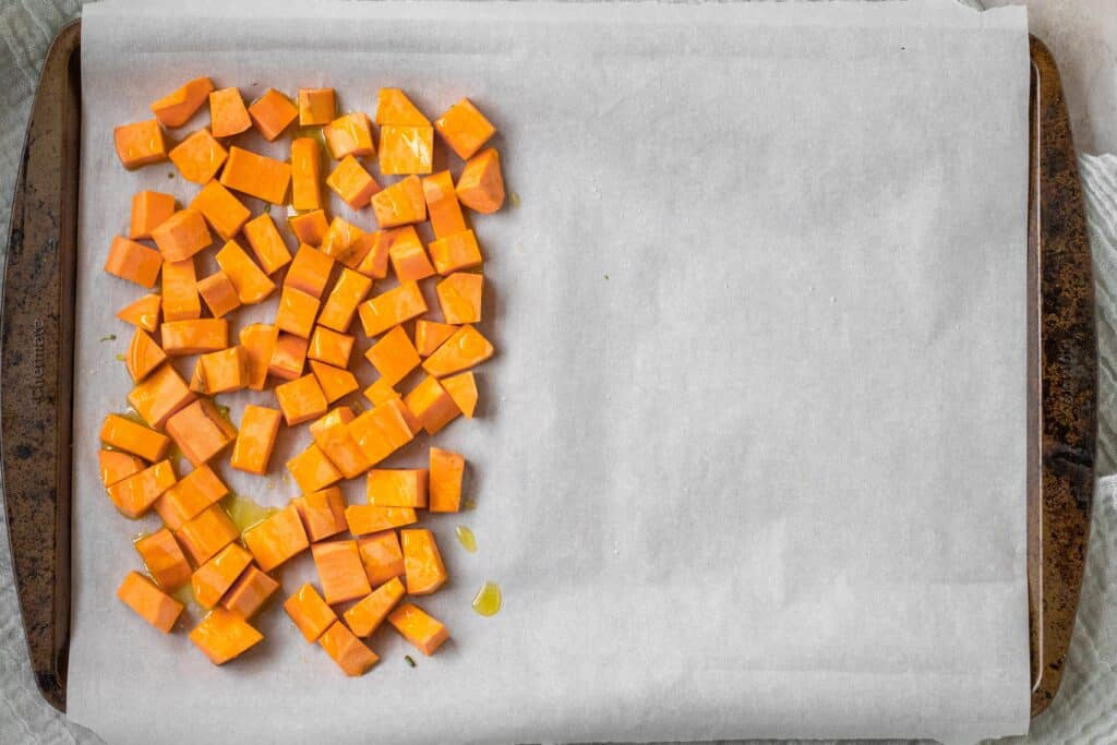 cut up sweet potato on parchment lined baking sheet