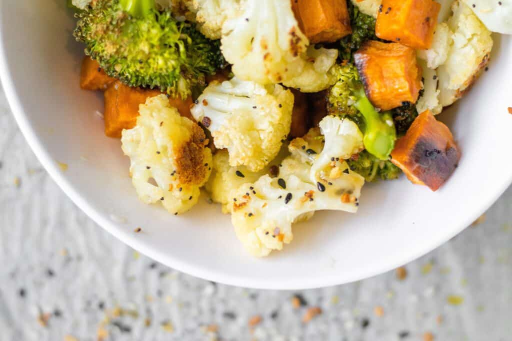 roasted sweet potato, cauliflower and broccoli in a white bowl