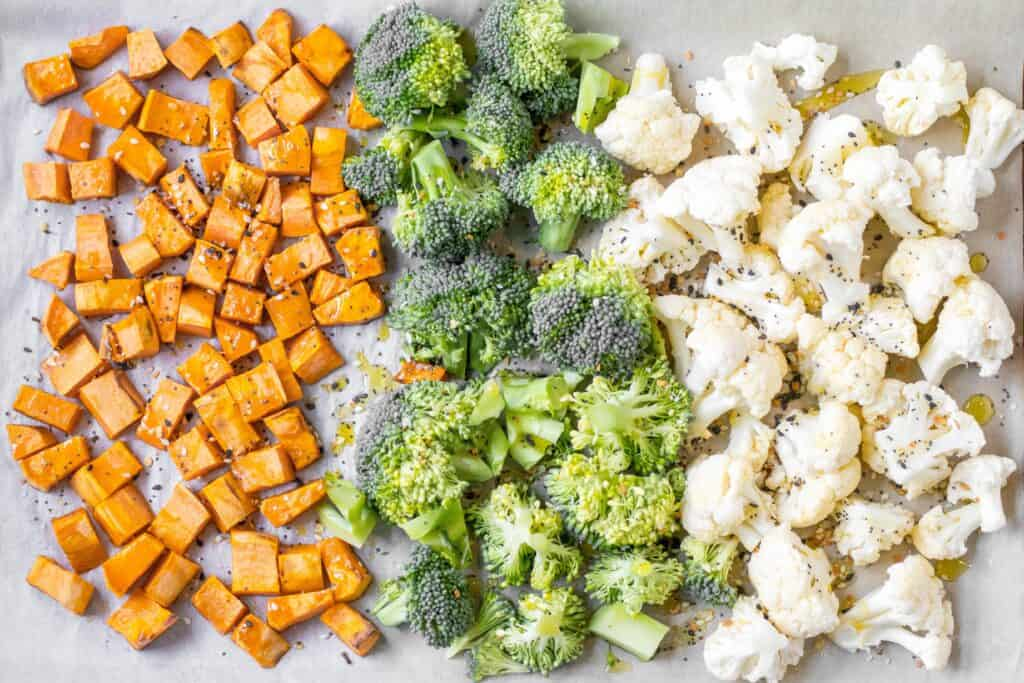 cut up sweet potatoes, broccoli and cauliflower on a sheet pan