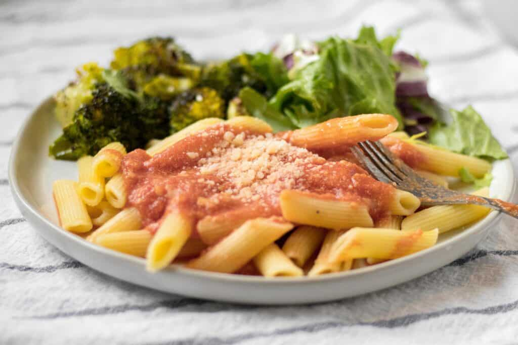 pink sauce pasta on a plate with salad and broccoli