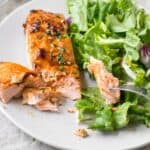 salmon cut into with a fork and salad