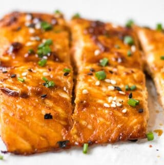 3 pieces of sesame ginger salmon garnished with black and white sesame seeds and chives