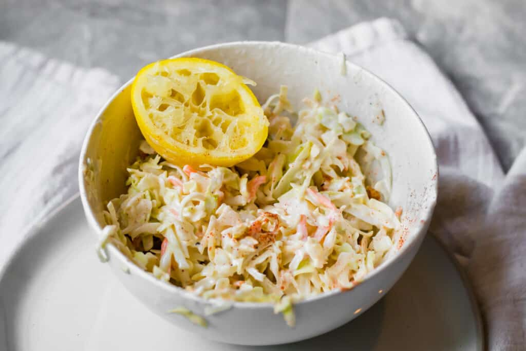 lemony slaw in a white bowl with a squeezed lemon