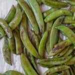 blistered sugar snap peas on parchment paper