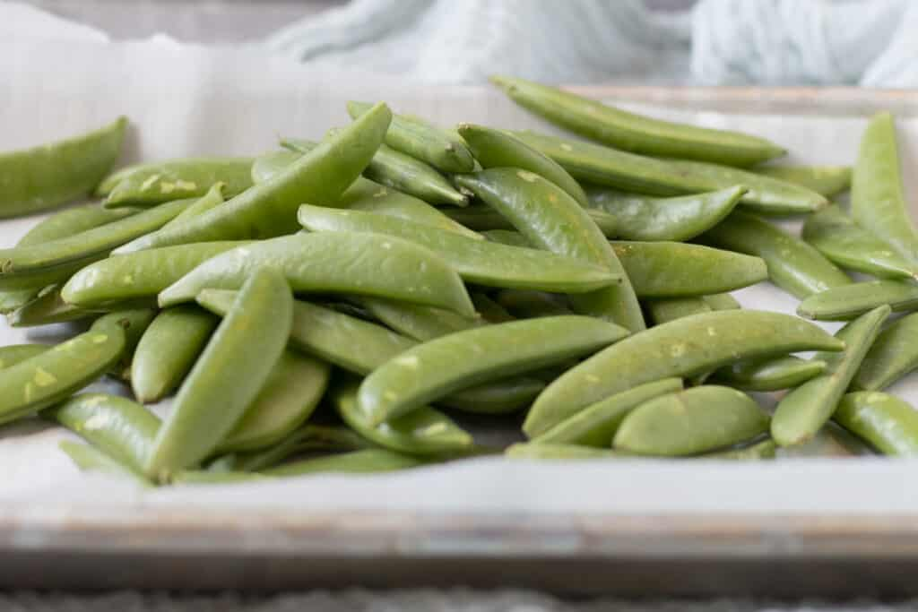 raw sugar snap peas on parchement paper
