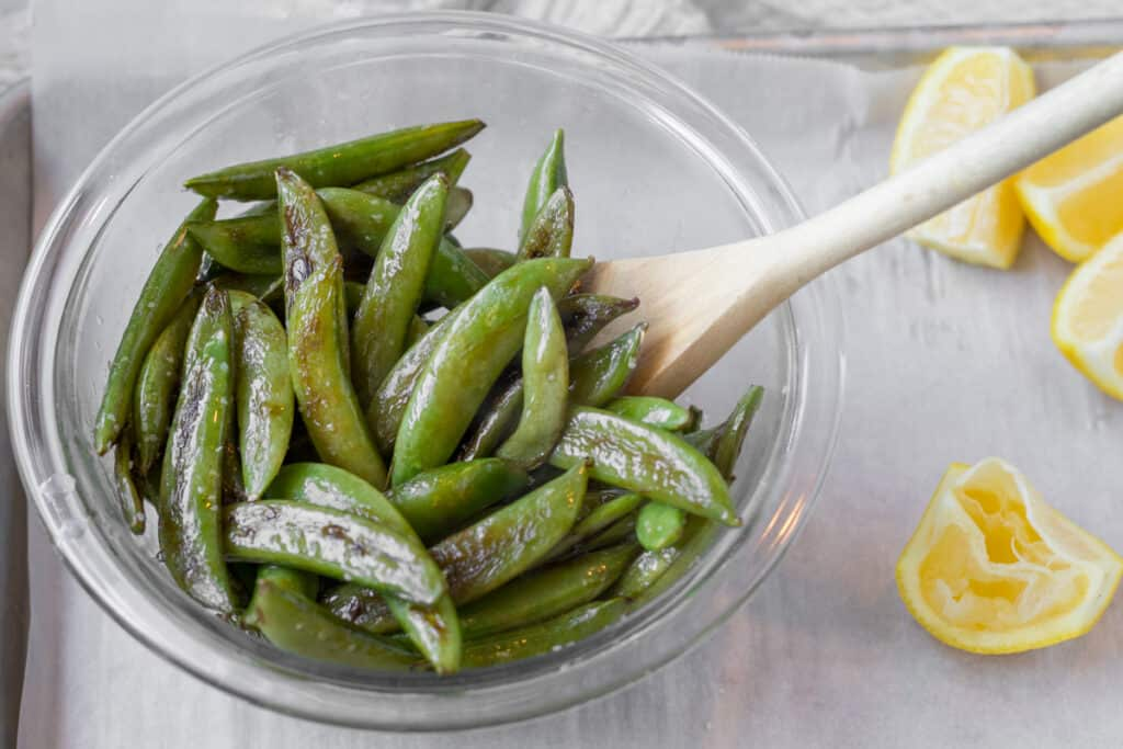 blistered sugar snap peas in a glass bowl with wooden spoon and squeezed lemon