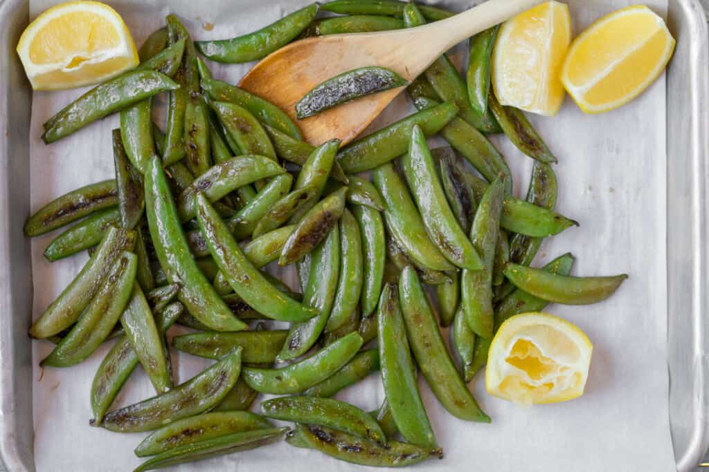blistered sugar snap peas with a wooden spoon and squeezed lemon