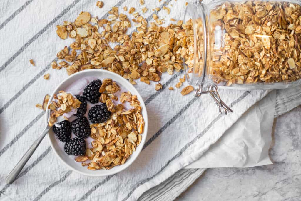 granola spilling from glass jar next to a bowl with yogurt fruit and vanilla almond granola