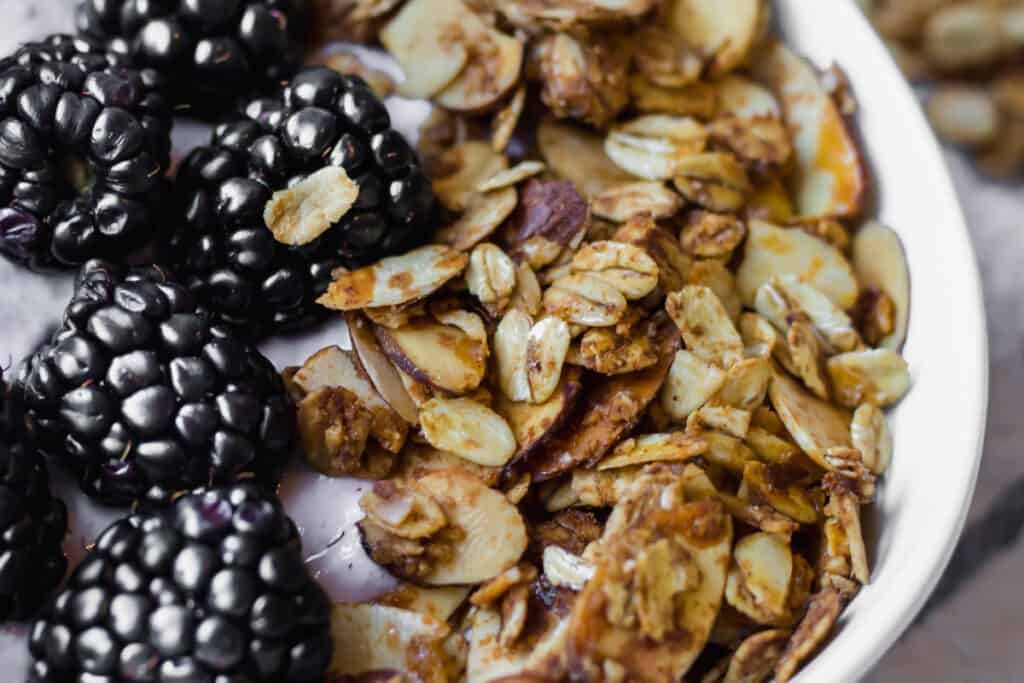 close up of granola and blackberries in a bowl of yogurt