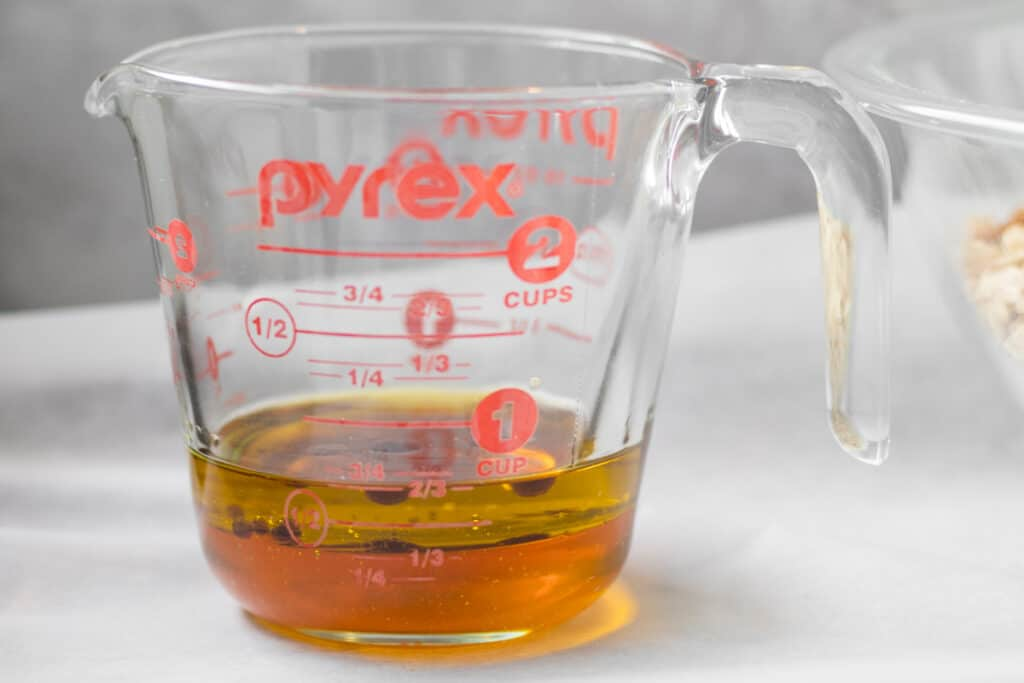 honey, vanilla and oil in a glass measuring cup