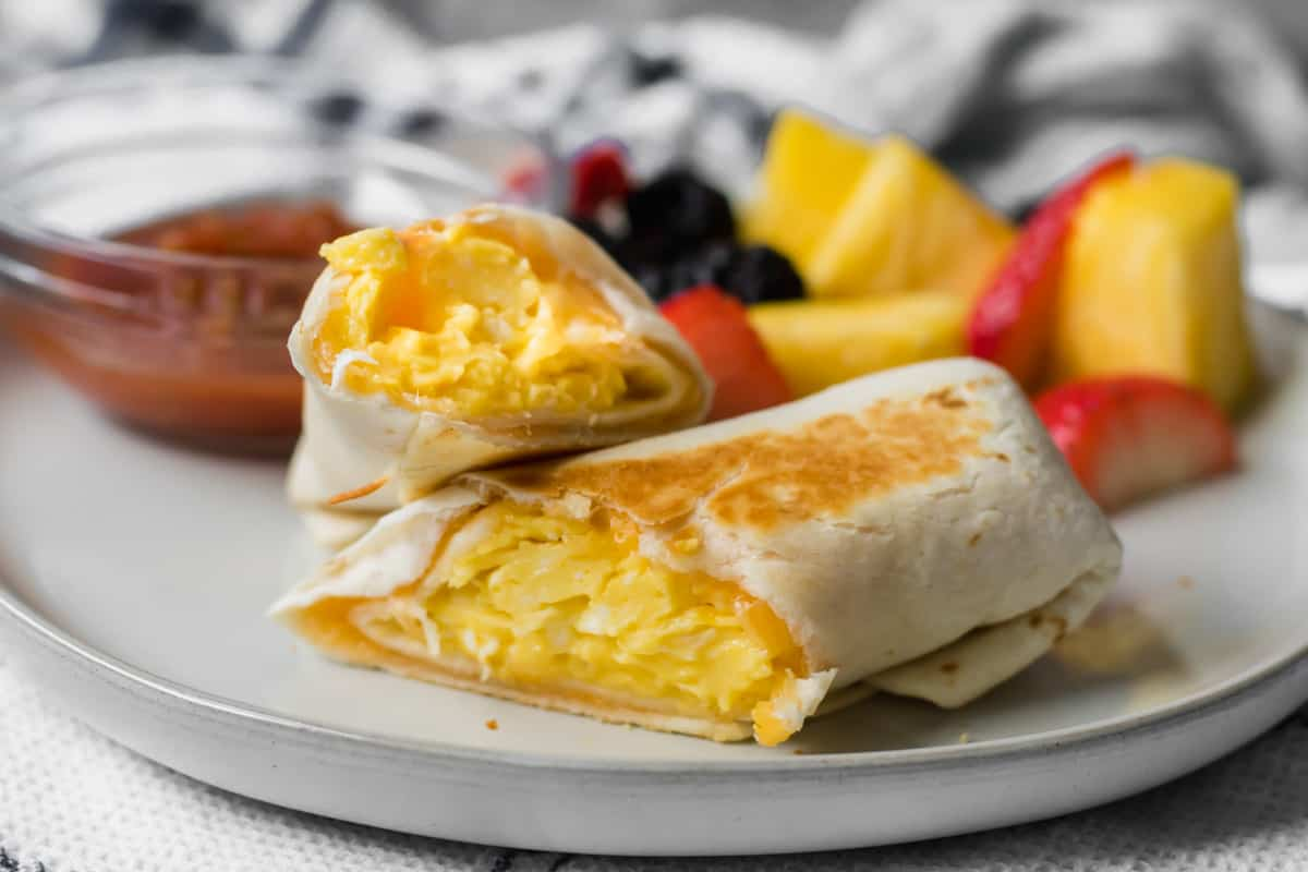 cheesy breakfast burrito on a plate with fruit and salsa