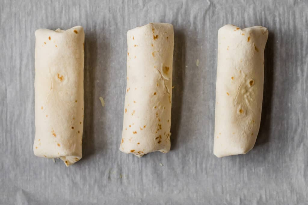 three rolled breakfast burritos on a parchment lined sheet tray