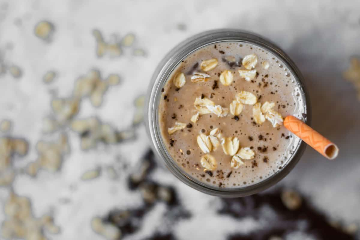 overhead of coffee smoothie in mason jar with oats and coffee on top