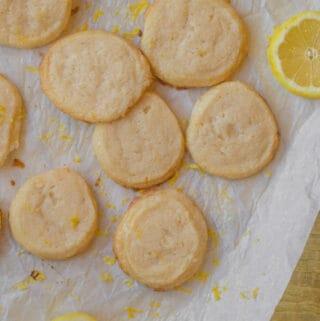 lemon shortbread cookies with a slice of lemon on parchment paper