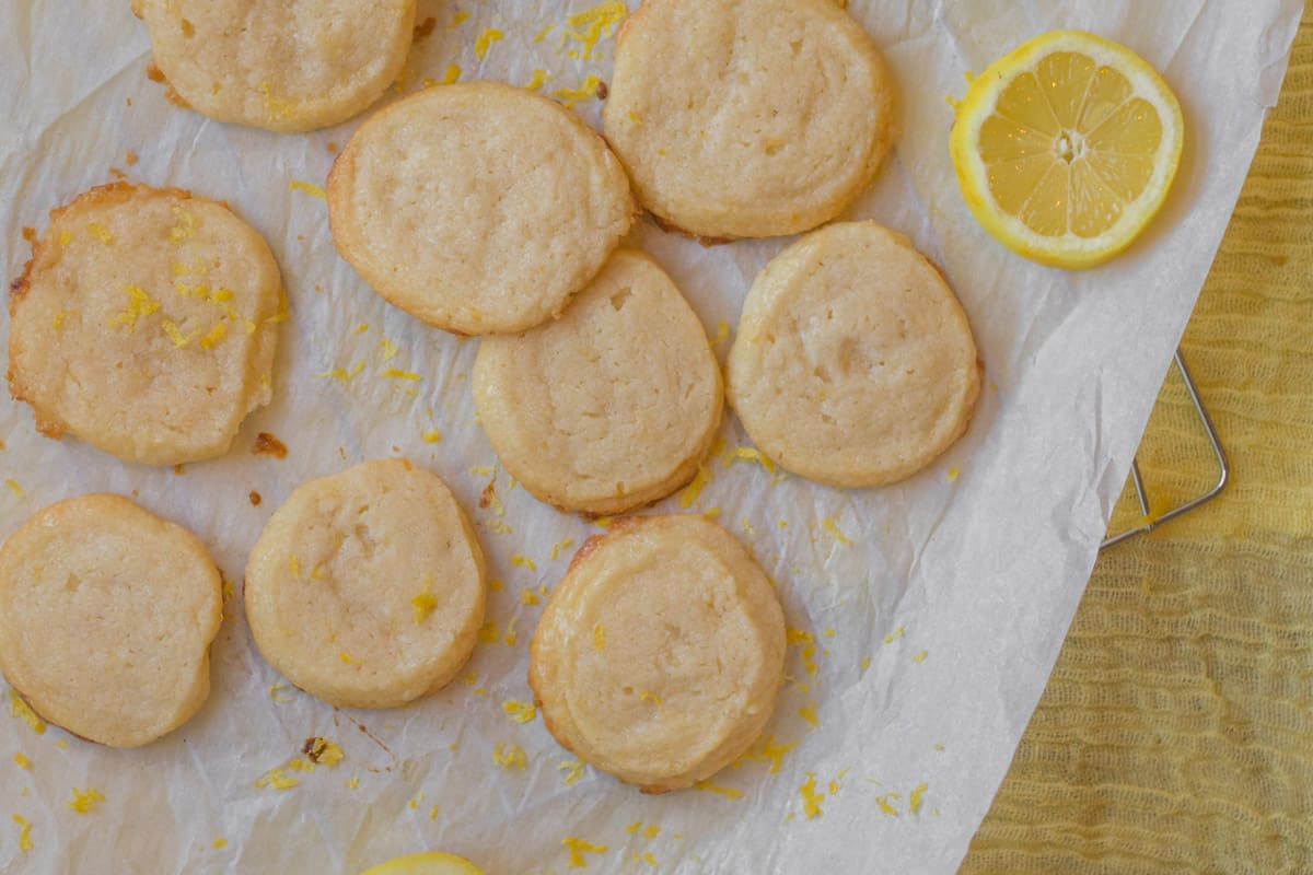 lemon shortbread cookies with a slice of lemon on parchment paper
