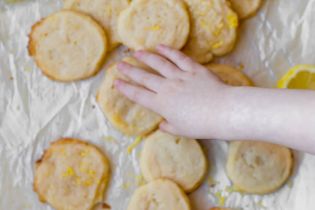 lemon short bread cookies with a kids hand trying to steal one