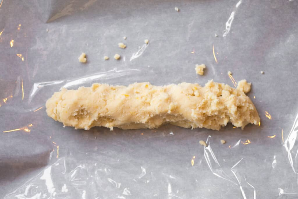 log of dough laying on cling wrap