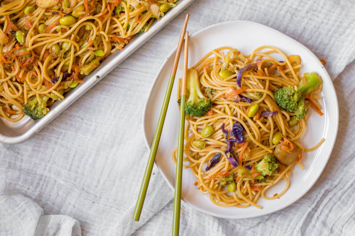 green chopsticks and homemade veggie lo mein on a white plate