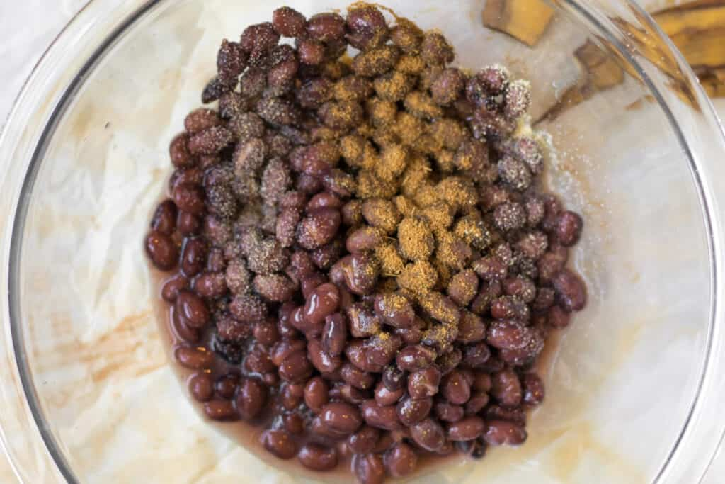black beans in a bowl with cumin and salt