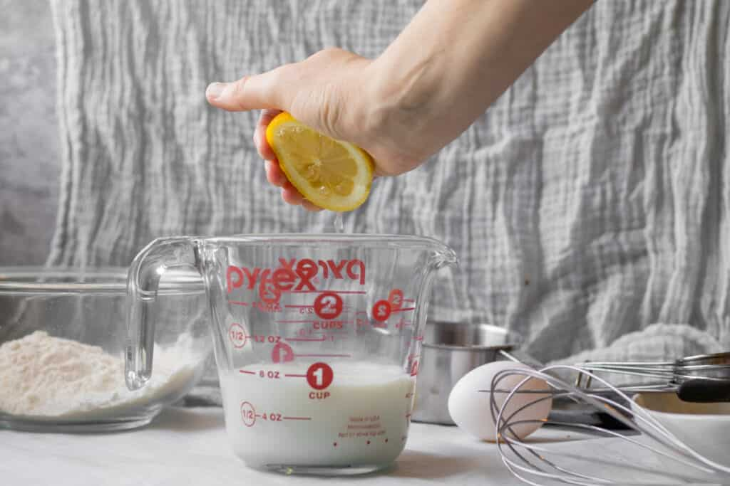 lemon being squeezed into milk