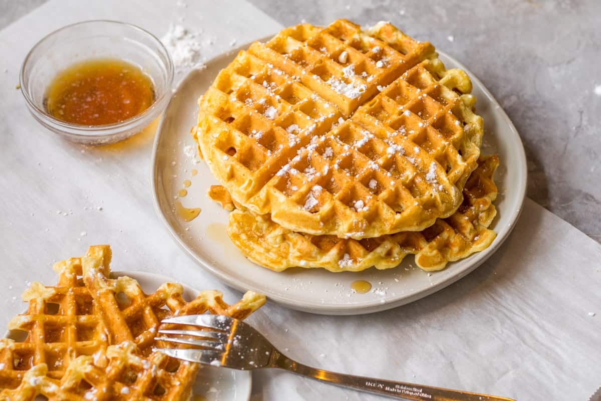 stack of waffles on a plate with syrup