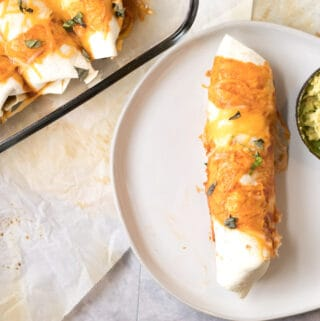 goat cheese, black bean and plantain enchilada on a plate with half an avocado